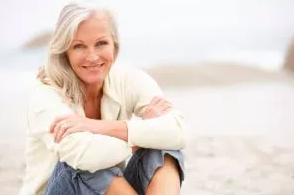 image of woman sitting on the beach smiling